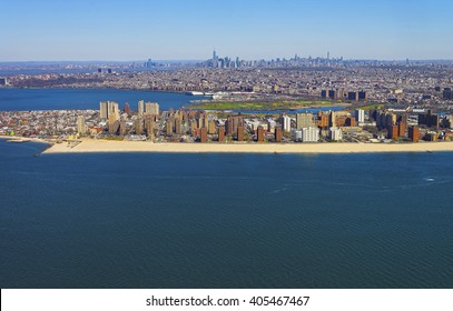 Helicopter view on Coney Island Beach and Boardwalk, Brooklyn, New York City, USA. Washed by Coney Island Channel and Coney Island Creek. Lower Manhattan is far on the background