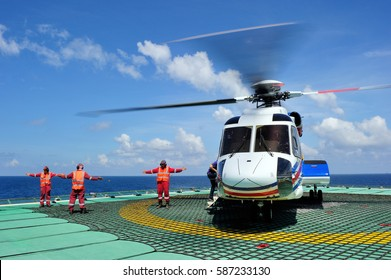 Helideck crew members working on the helipad at an offshore platform while boarding passengers