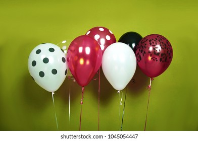 Helium balloons party decoration isolated on green background