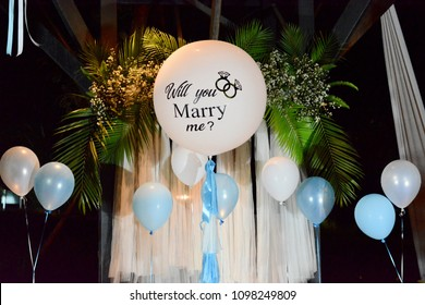 Helium-filled balloons decorated for proposal of marriage in theme of white and blue night.