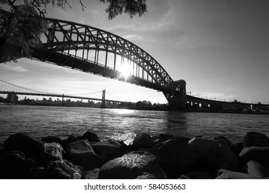 The Hell Gate Bridge and rocks, And the sun reflects on the river in black and white style, New York