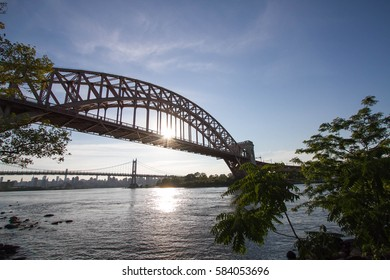 The Hell Gate Bridge and the sun reflect on the river behind the tree, New York
