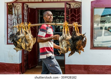 HELL VILLE, MADAGASCAR - DECEMBER 19, 2015: Malagasy vendor carries chickens to the market in Hell Ville, a town at the Nosy Be island, North of Madagascar.