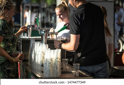 Hellevoetlsuis,Holland,09_aug_2019:man tapping a beer for a woman on a oudoor party in Hellevoetlsuis, the outdoor party is a anual activity