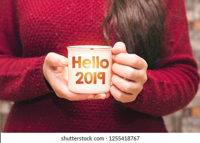 hello 2019 text on cup and woman drinking a coffee