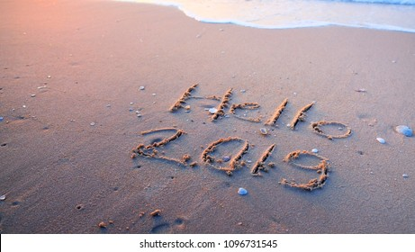Hello 2019 written on sand beach in the morning.