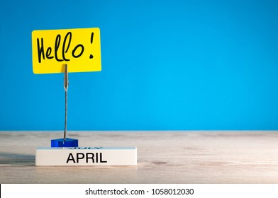Hello April - an inscription reminder of the month's arrival on the table, blue background, with empty space for text, mockup or template.