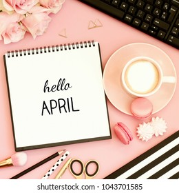 Hello April text on notebook. Office desk table   with cup of coffee, sweet snacks, computer and pink flowers. Pink, gold, black and white tones. Top view, flat lay.