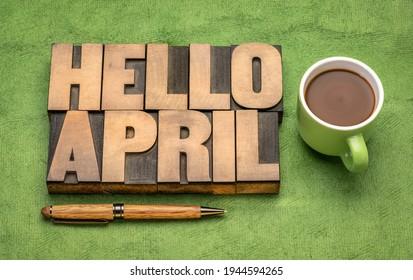 Bonjour le mot d'avril abstrait dans le type de letterpress vintage avec une tasse de café contre du papier vert fait main, salutations gaies
