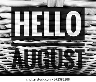 Hello August words on black and white wood chair background.