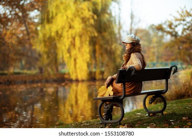 Hello autumn. Full length portrait of pensive young woman in sweater, skirt, hat, gloves and scarf with yellow leaves while sitting on a bench outdoors in the autumn park.