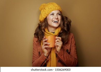 Hello autumn. happy elegant woman in yellow beret and scarf with cup of pumpkin latte isolated on brown background.
