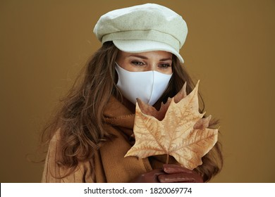 Hello autumn. pensive stylish woman in sweater with white medical mask and yellow autumn maple leaves on beige background.