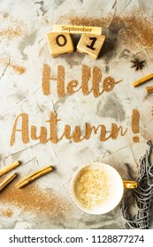 Hello, Autumn. The phrase is written with ground cinnamon on a gray background. Next to the wooden calendar on which the date is September 1. Top view, flat lay