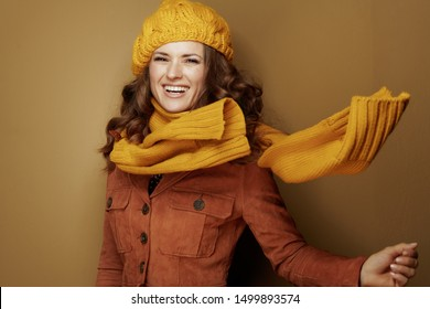 Hello autumn. Portrait of 40 year old woman in yellow beret and scarf on bronze background.