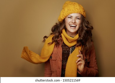 Hello autumn. Portrait of cheerful elegant woman in yellow beret and scarf isolated on brown background.