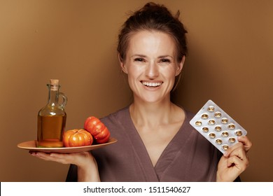 Hello autumn. Portrait of happy elegant middle age woman in a bathrobe with pumpkin oil and blister package of vitamins on bronze background.
