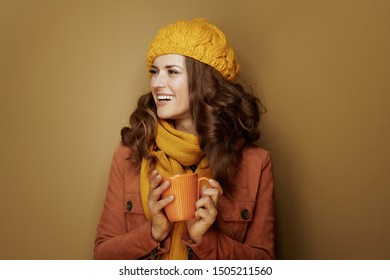 Hello autumn. Side view of happy modern woman in yellow beret and scarf with cup of soy latte looking at copy space isolated on beige.