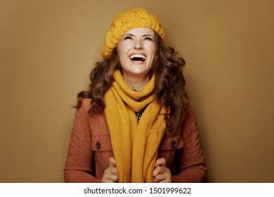 Hello autumn. smiling modern woman in yellow beret and scarf looking up on copy space isolated on beige background.