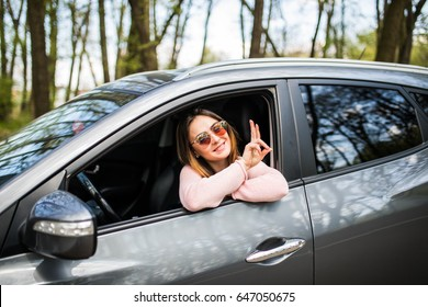Hello. Beautiful young cheerful women looking at camera with smile and waving while sitting in her car