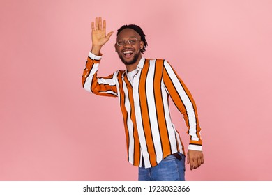 Hello! Cheerful friendly afro-american man with dreadlocks in bright striped shirt and denim pants saying hi and waving hand, greeting. Indoor studio shot isolated on pink background