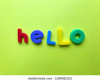 Hello. Colorful word. Magnetic letters on green background.