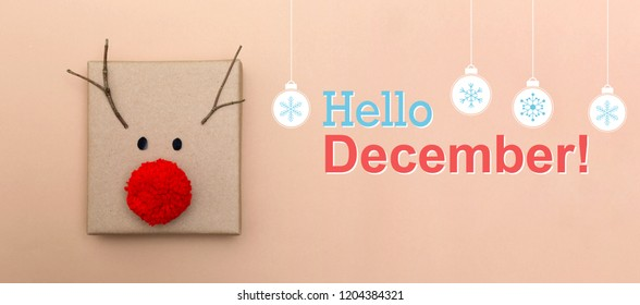 Hello December message with a red nose reindeer gift box