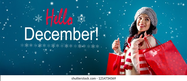 Hello December message with young woman holding shopping bags