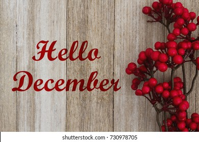 Hello December text on red floral holly berry spray on weathered wood