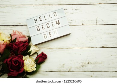 Hello December Word on Light box with roses flower bouquet on wooden background