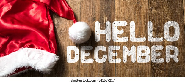 Hello December written on wooden background with Santa Hat