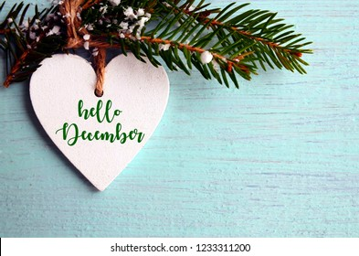 Hello December.Decorative white wooden Christmas heart and fir tree branch on blue wooden background. Winter holidays concept with space for text.Selective focus.