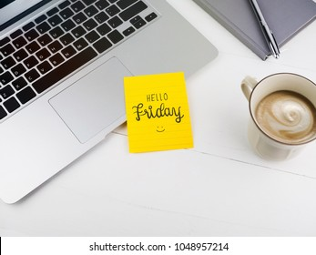 Hello Friday with smiley icon face on sticky note on desk