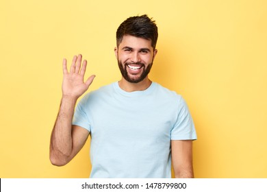Hello Hi Young cheerful handsome bearded man greeting with open hand, enjoying communication, isolated on yellow background. close up portrait, body language.