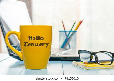 Hello January written on yellow coffee cup at manager or freelancer workplace. New year time concept. Business and office background