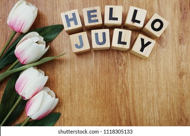 hello july with artificial flower on wooden background