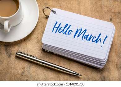 Hello March! Handwriting on a stack of index cards with a cup of coffee and  a pen