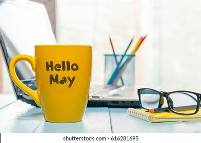Hello MAY - text on yellow coffee cup at business office background, workplace with laptop and glasses. Spring time, empty space for text