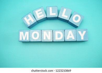 hello monday with blue wooden cubes alphabet letter on blue background