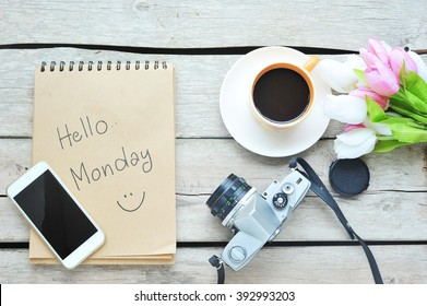 Hello Monday - Coffee with smartphone,camera on wooden table.