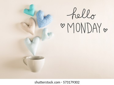 Hello Monday message with blue heart cushions coming out of a coffee cup