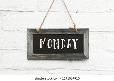 Hello monday text on hanging board white brick outdoor wall