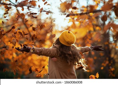 Hello november. smiling modern woman in brown coat and yellow hat rejoicing outside on the city park in autumn.