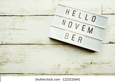 Hello November Word on Light box with roses flower bouquet on wooden background