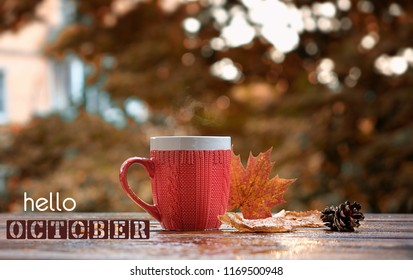 Hello october card. beautiful autumn composition. autumn leaves and cup of tea on rustic wood background. concept of the fall season. soft selective focus