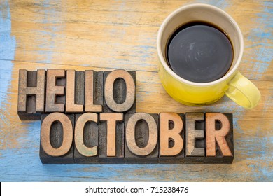 hello October greeting card - vintage letterpress wood type blocks against grained wood with a cup of coffee