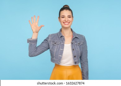 Hello! Portrait of friendly sociable woman in stylish casual clothes gesturing hi, welcoming with raised hand and looking at camera with affable smile. indoor studio shot isolated on blue background