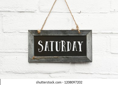 Hello saturday finally weekend text on hanging sign board against white brick outdoor wall