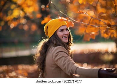 Hello september. happy trendy woman in brown coat and yellow hat having fun time outdoors in the city park in autumn.
