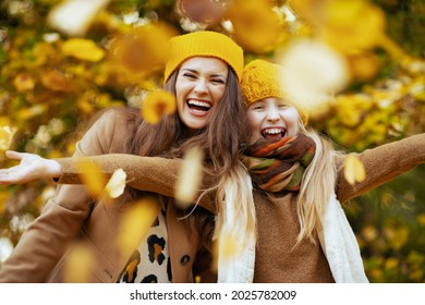 Hello september. happy young mother and child in yellow hats outdoors on the city park in autumn rejoicing.